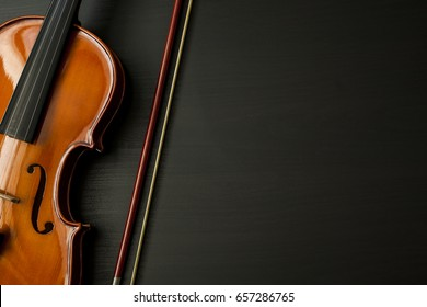 Violin and bow on a dark wooden table