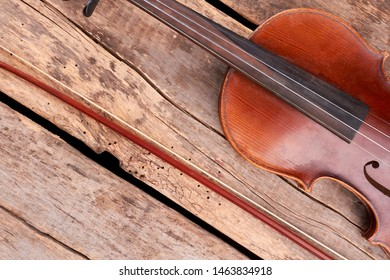Violin and bow on wooden floor. Old violin and fiddle stick on rustic wooden planks. Musical equipment of orchestra.