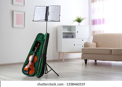 Violin in case and note stand with music sheets in room
