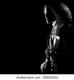Violin concert party. Silhouette of violinist on black background. Black and white artistic photo