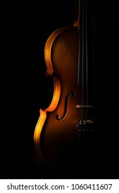 Violin detail on a black background between light or shadows.