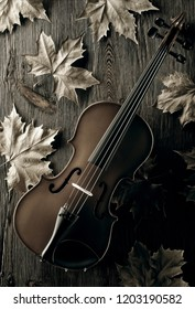 violin with fall leaves on aged wood background