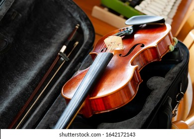 Violin, fiddle with a bow laying in an open black case on the table, small xylophone in the back. Simple classical musical string instruments group concept, nobody. Safe instrument storage for travel