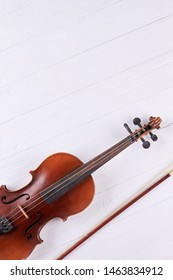 Violin, fiddle stick and copy space. Classical musical instrument on white wooden surface with text space.