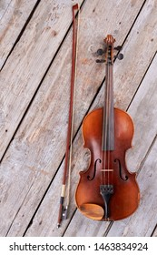 Violin and fiddle stick on wooden background. Brown violin and bow on old wooden boards.