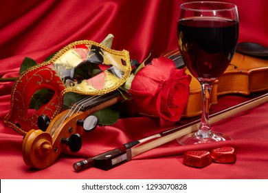 Violin (fiddle), theater mask, red heart, glass of wine and red rose lying on the perfect red satin fabric. String instrument. Valentine's day.