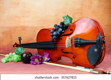 A violin with grapes and flowers