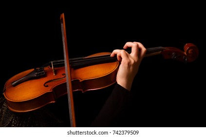 Violin in the hands of musician, isolated on black background