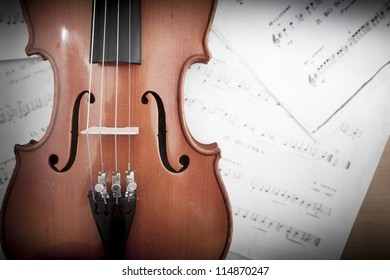Violin laying on music notes