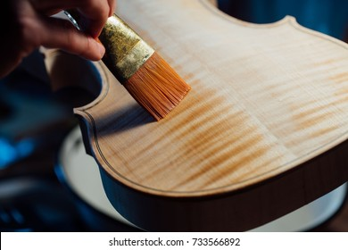 violin maker varnishing a violin body close up. orange brush leaves a wet trace on the wood texture. Atmospheric handmade master work.