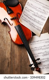 Violin and music papers on wooden background
