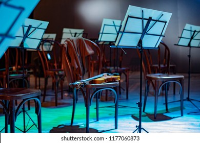 Violin and music stand. Violin on a chair and music stands with notes around. the orchestra is on break. sweater on the back of a chair