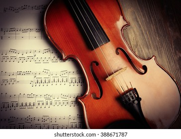 Violin and musical notes on wooden background