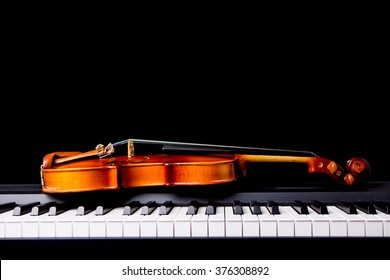 Violin on the piano on black background