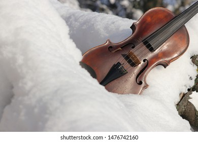 Violin on snow - theme (motive) Christmas, Xmas, advent. Concept background for music, instrument, winter. Old antique violin is outside (outdoors) on snow. Free place (empty, copy space) for text.