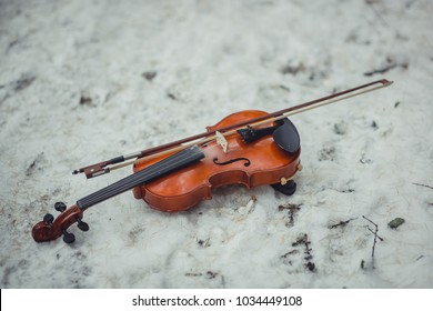 The violin  on snowy ground in winter park