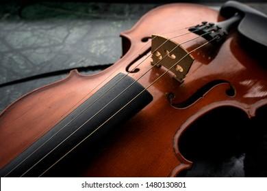 Violin ,Violin on the table dark background ,Violin waist detail on rustic dark background