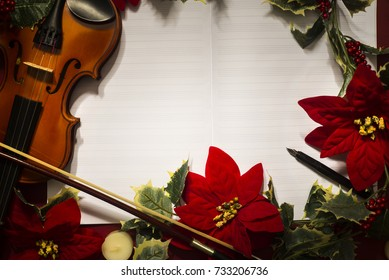 Violin and open music manuscript on the red background. Christmas concept. Copy space