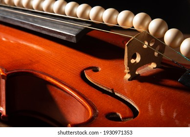 Violin and pearl necklace, arrangement with violin and pearl necklace on wooden surface, low key portrait, selective focus.