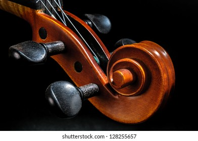 Violin pegbox and scroll detail view on black background