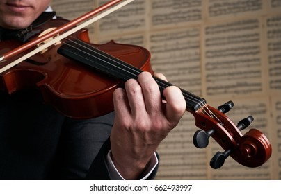 Violin player hands. Musician, virtuoso, violinist playing violin against the background of musical notes. Close up of musical instruments, fiddle with fiddlestick