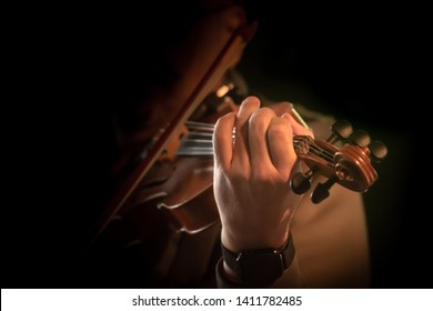 Violin playing musician in closeup in front of black background. Fiddler in action.