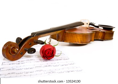 A violin a rose and sheet music on a white background, focus is on the peg head of the violin and the rose