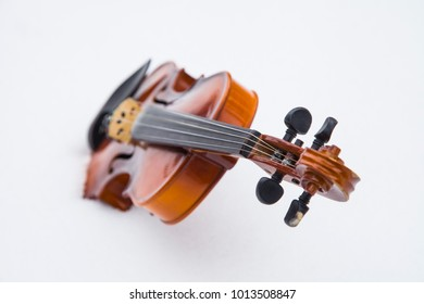 Violin in the snow, isolated on light background, closeup, shallow depth of field