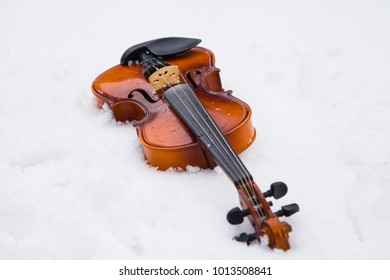 Violin in the snow, shallow depth of field, closeup