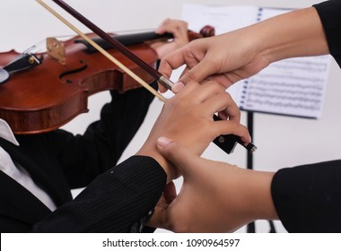 The violin teacher hands is teaching the violin student,by touch student hand for using bow to play on string ,blurry light design background.