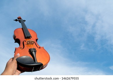 Violin with a wall background. Having an all round vintage theme. Closeup shot of an acoustic violin.