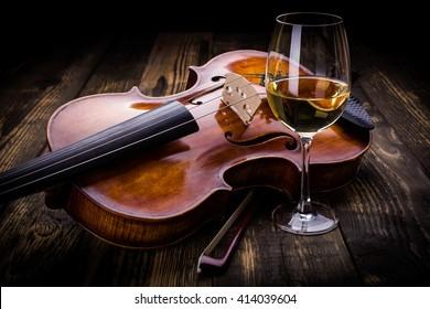 Violin and wine on dark wooden background