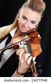Violinist girl playing on violin over dark background