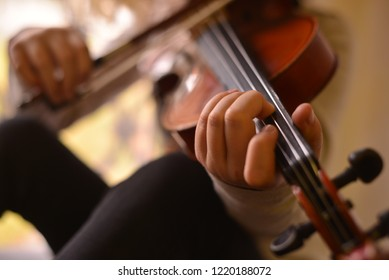 The violinist hand on strings in detail while playing.