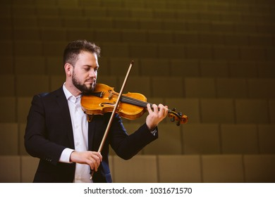 Violinist. Image of a man violinist in a concert hall. The young violinist wears a suit.