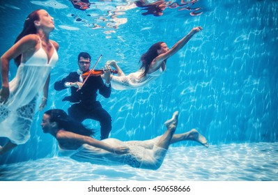 Violinist playing underwater with muse swimming around in the pool