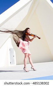 Violinist plays on the stage under the open sky in a pink dress