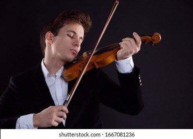A violinist plays the violin in a Symphony orchestra concert, a musician emotionally plays classical music on a wooden instrument
