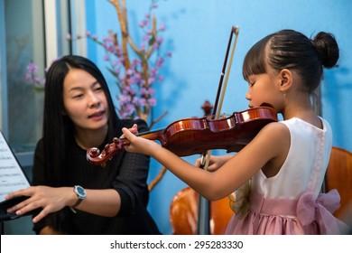 Violinist teacher teach student with violin in studio school.