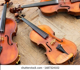 Violins on a wooden background. Two violins and viola.