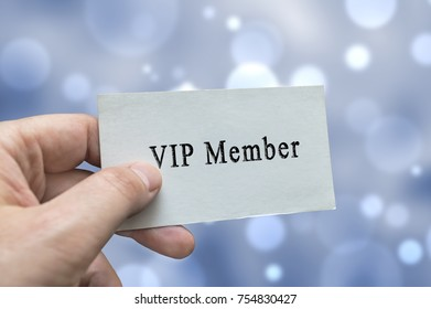 VIP Member card in hand with blurred bokeh lights in the background
