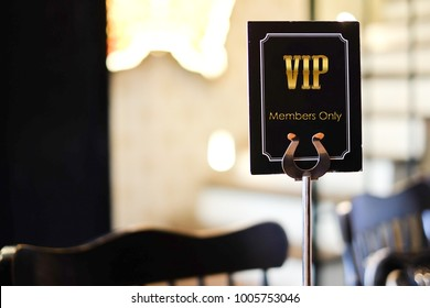 VIP sign on a table in restaurant, hotel or cafe. On the black label. The sign is on the table.  label VIP club party premium invitation. alphabet Black and golden design