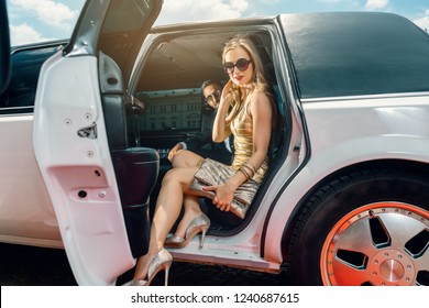 VIP Woman and man getting out of limousine with door being open