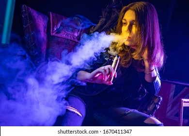 Viper girl is sitting in a chair. Student on a dark background smokes a vape. Young woman with a vape device. Concept - sale of vaping liquids. Blowing smoke through the nose. Electronic cigarette