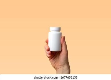Viral disease prevention concept. Female hand holds jar with vitamins, pills, medicines or drugs on orange background. Coronavirus prevention. Safety rules during quarantine. Copy space for text