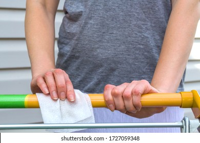 Viral disease prevention concept. Woman wipes down a handle of public shopping cart with a disinfecting moist towelette in mall or supermarket. Coronavirus prevention, safety rules during the epidemic
