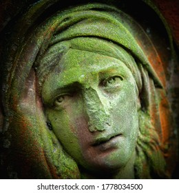 Virgin Mary. Ancient stone statue of sad woman in grief