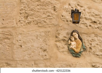 Virgin Mary and a child Small statue of Virgin Mary and a Child under a lantern on a texture wall of a house at the mediterranean island Malta.