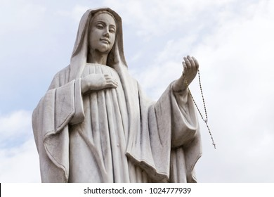 Virgin Mary statue holding rosary in hand with blue clear sky background stands in front of the Roman Catholic Church Pfarrkirche St. Alban in Matrei in Osttirol