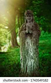 Virgin Mary statue. Very old and ancient stone statue of sad woman in grief
